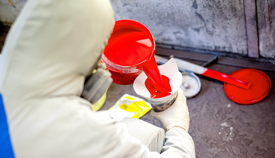 Auto mechanic mixing and pouring red paint for spray booth